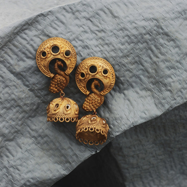 Our Nritya earrings made with unpolished brass placed on a grey background.