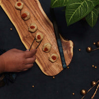 Dim sums placed on our wooden platter and a model using the cane tongs in blue to pick them up.