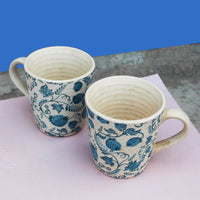 Blue floral cozy together mugs placed on a pink and blue background