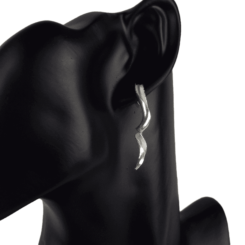 The silver variant of the earrings in wear on a mannequin.