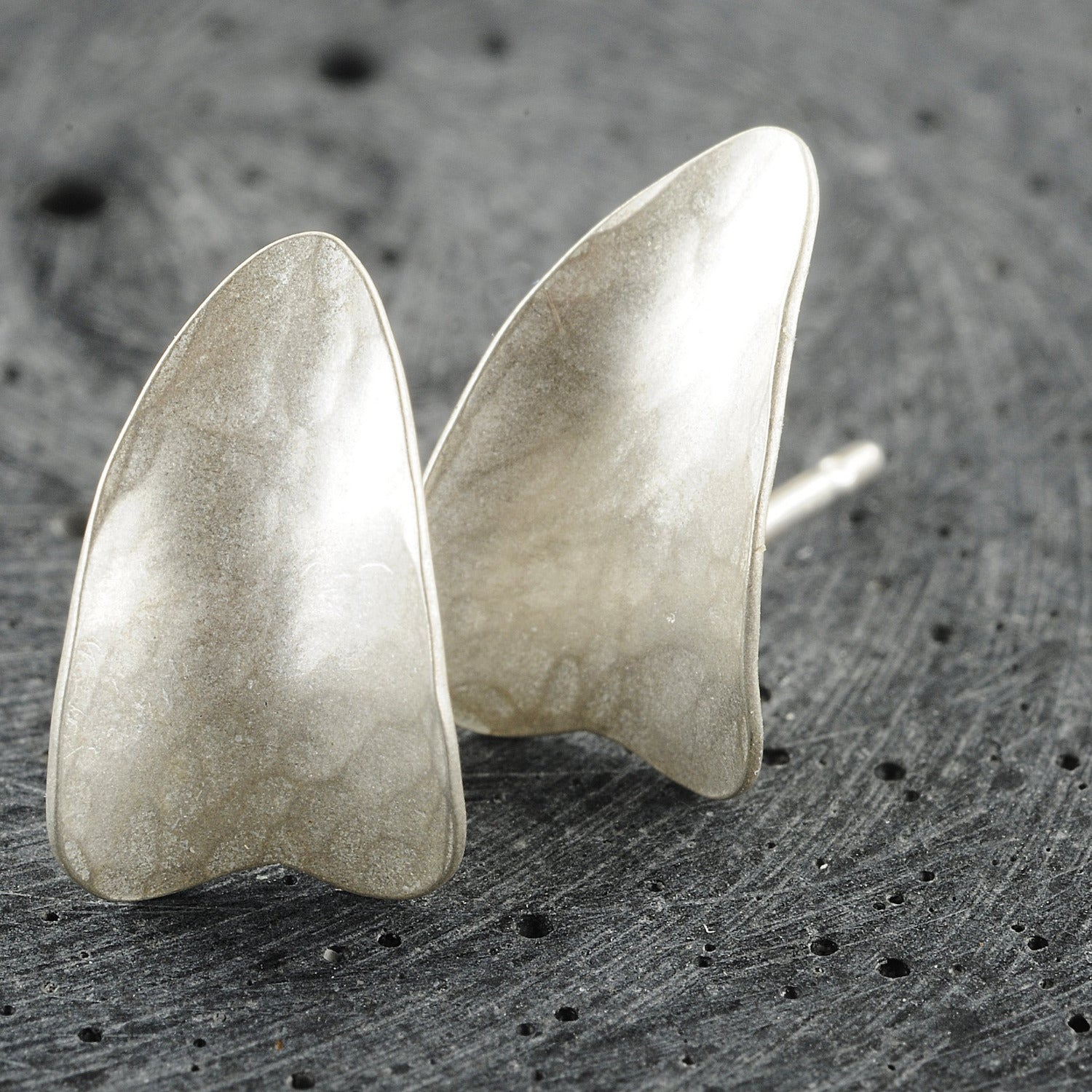 Silver heart studs, showing the studs close together and upside down. Displays the curve of the studs.