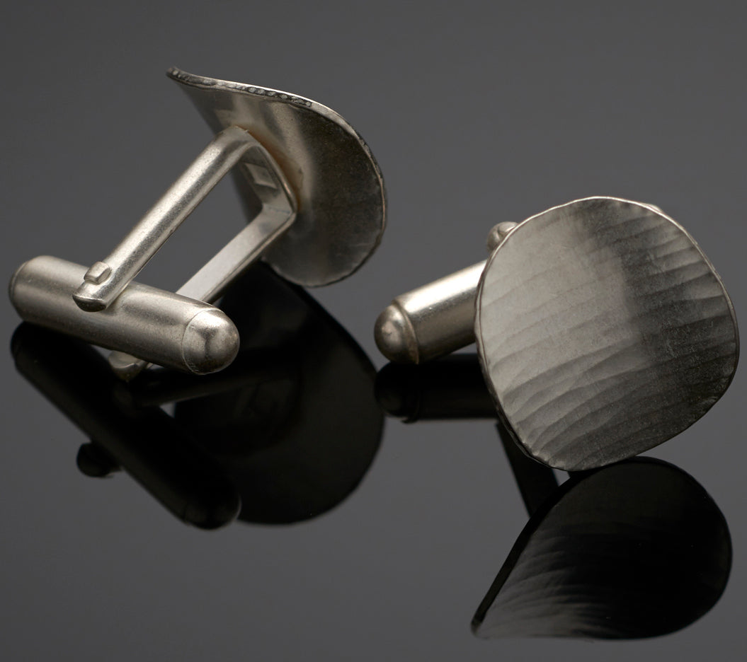 The oval cufflinks, showing the back of one with the attachment of the mechanism.