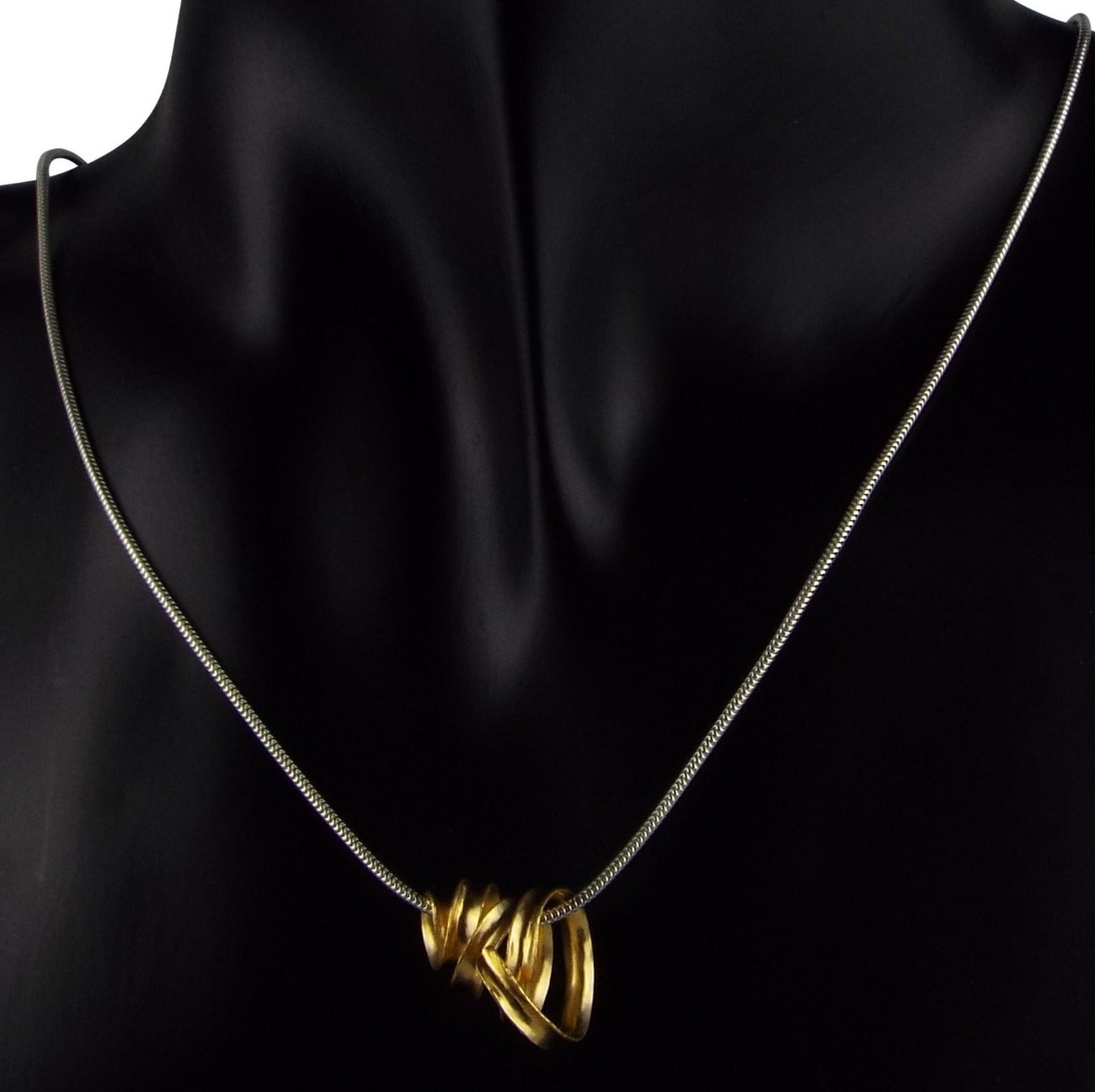 Gold vermeil ribbon pendant on silver snake chain, in wear on mannequin