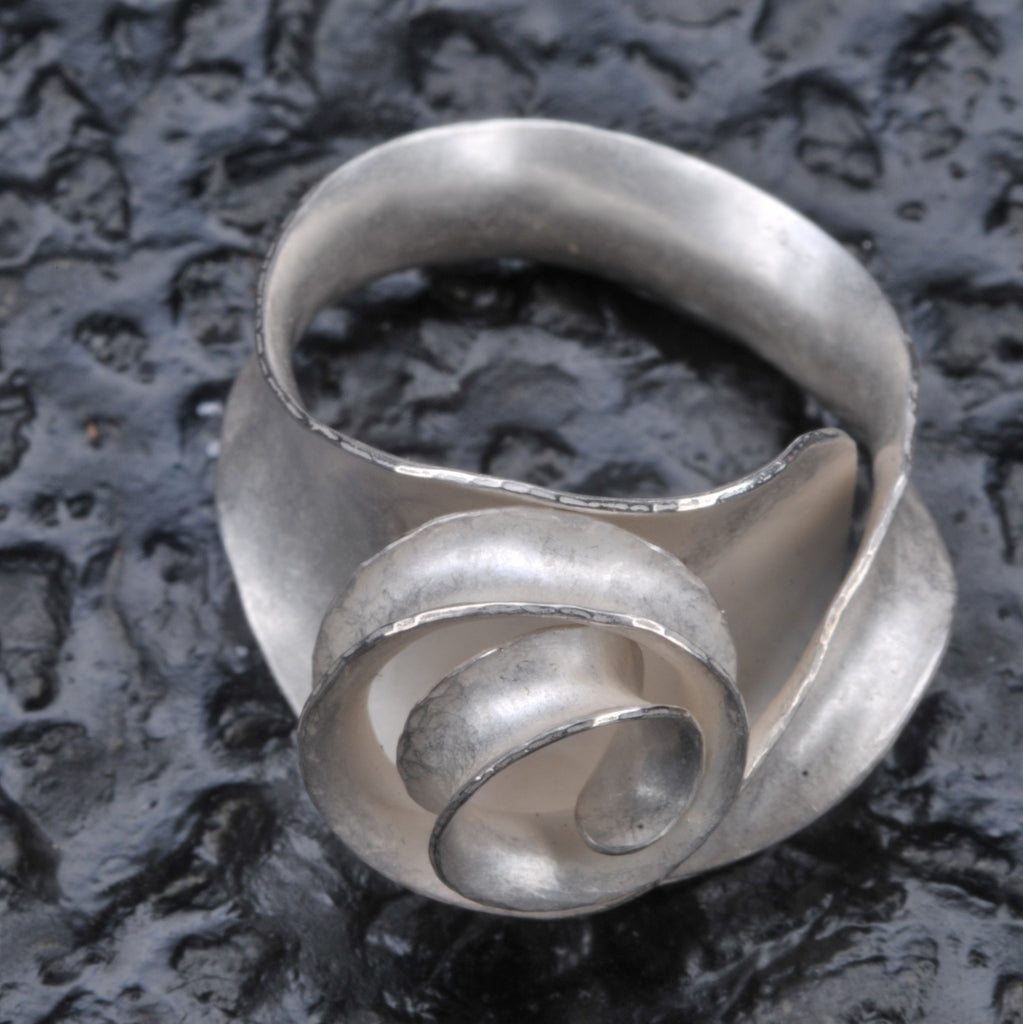 Scroll ring seen from the front and above against a dark, textured, glossy background