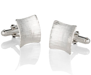 Open image in slideshow, A three-quarter view of the square cufflinks, showing the double curve, the hammered texture and the hinged mechanism