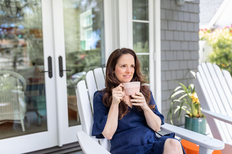 Brunette woman in navy dress drinking collagen latte