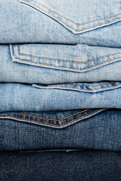 A stack of denim, from heavily faded to raw