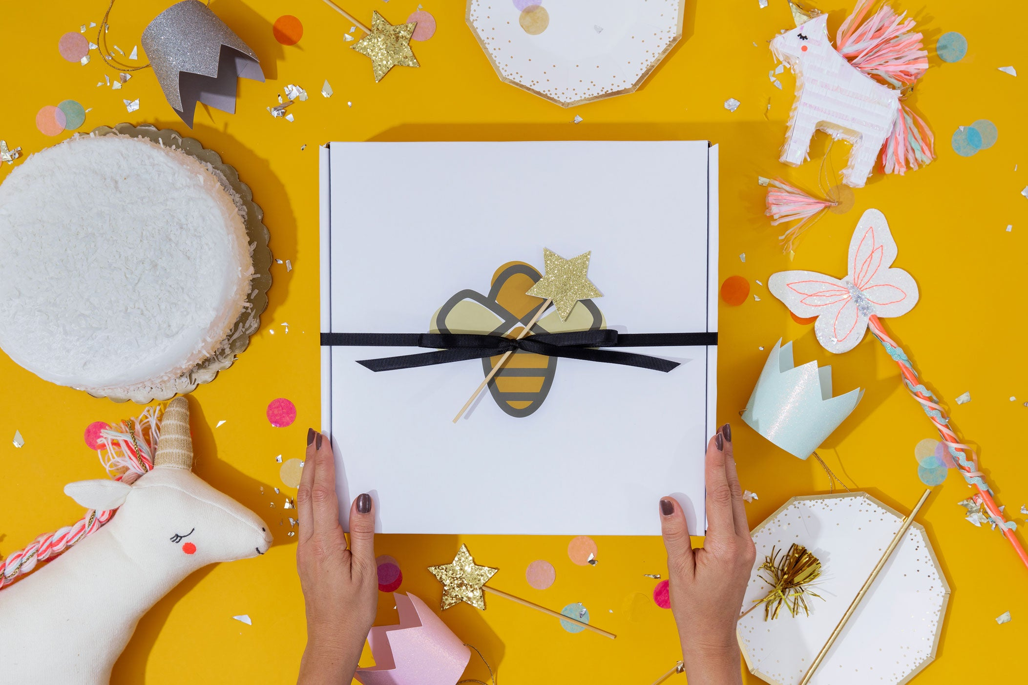 top down view of HoneBug box on yellow table surrounded by fun accessories