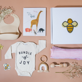An assortment of baby clothes and a gift box
