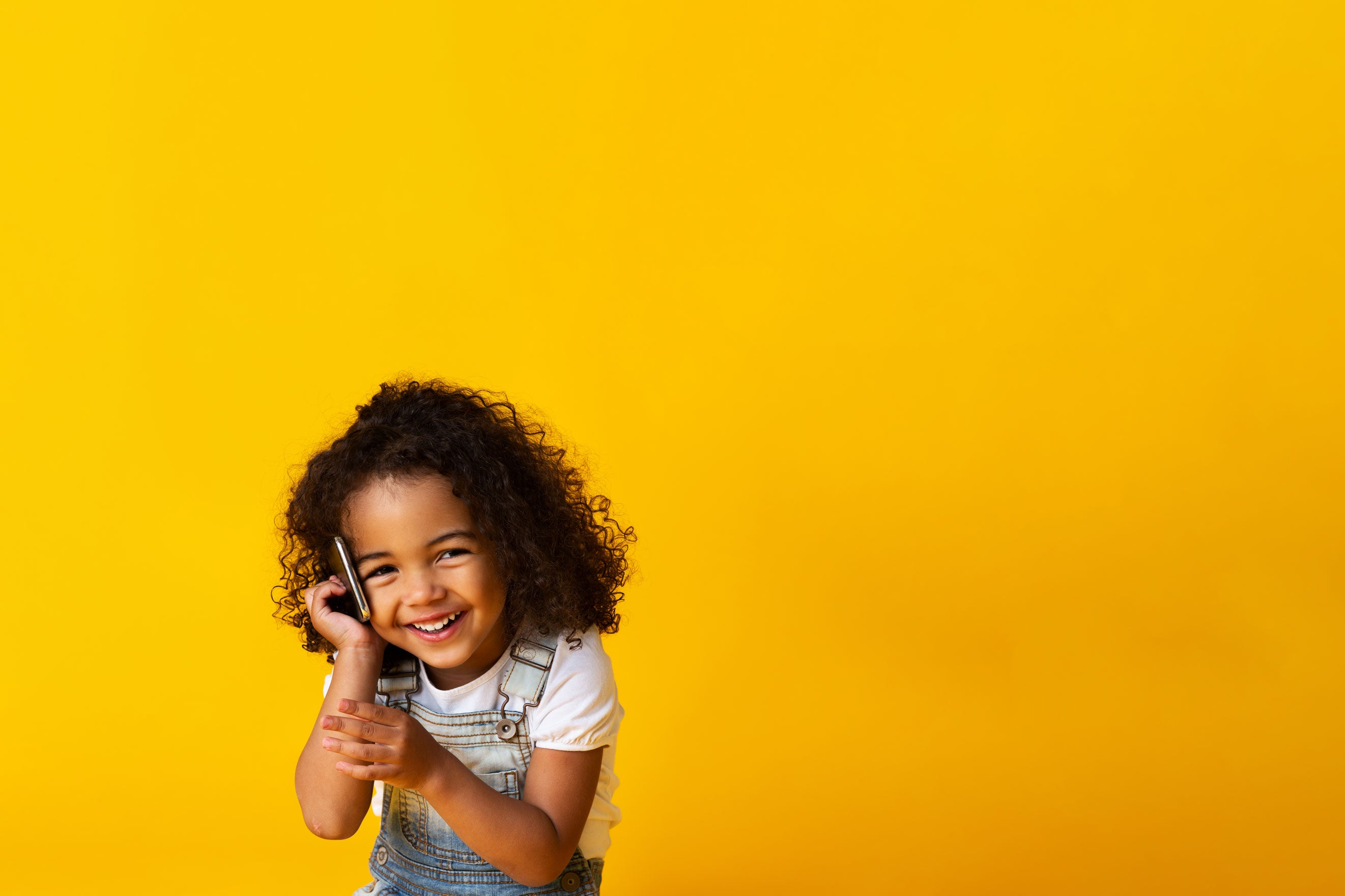 child with curly hair wearing suspenders smiling and holding smartphone to her ear against a yellow background