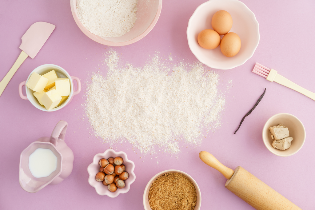 10 Ways To Show Your Cat Some Love This Valentine's Day overhead flat lay of pink table with baking supplies and flour
