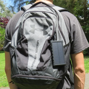 SunSaver 10K, 10,000mAh Solar Power Bank attached to a persons backpack.
