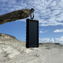 Load image into Gallery viewer, SunSaver 24K, 24,000mAh Solar Power Bank in the sun on the beach.