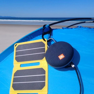 SunSaver Power Flex, 6.4-Watt Solar Charger charging a speaker at the beach camping.