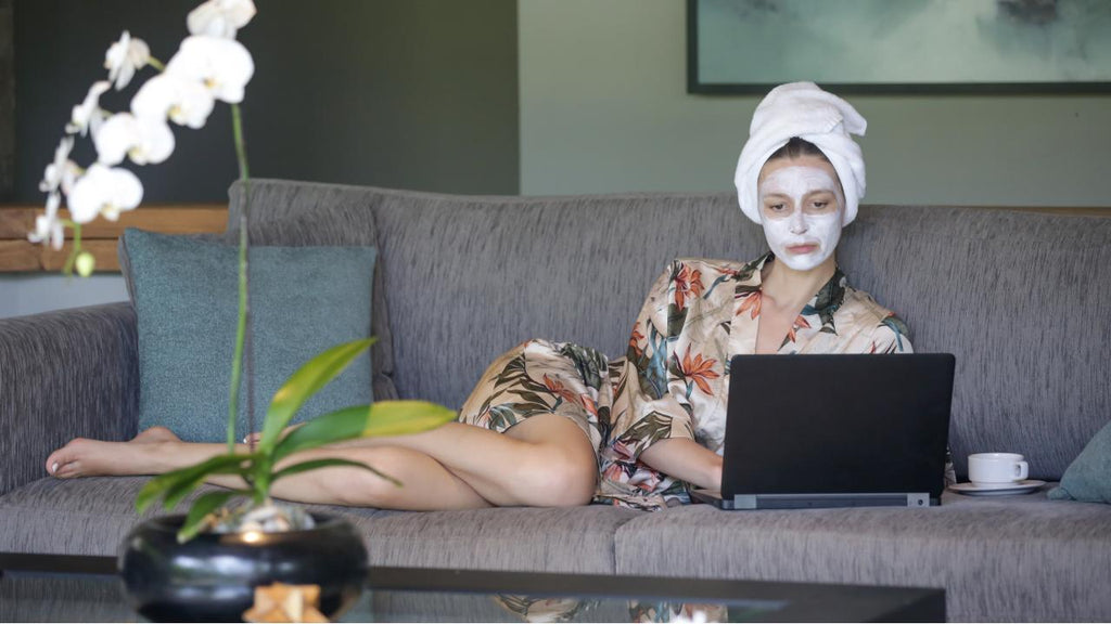 Woman spending time alone on the couch with a hot cup of tea, playing music on her laptop and enjoying a face mask.