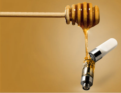 Image of CBD oil poured into a vape cartridge using a wooden honey dripper
