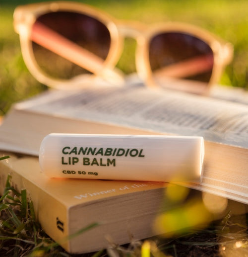 Image of Cannabidiol infused lip balm sitting on books with sunglasses in the background