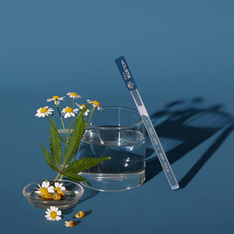 Lifestyle image of the HOLISTIK sleep STIK leaned up against a glass with some chamomile laying next to the glass