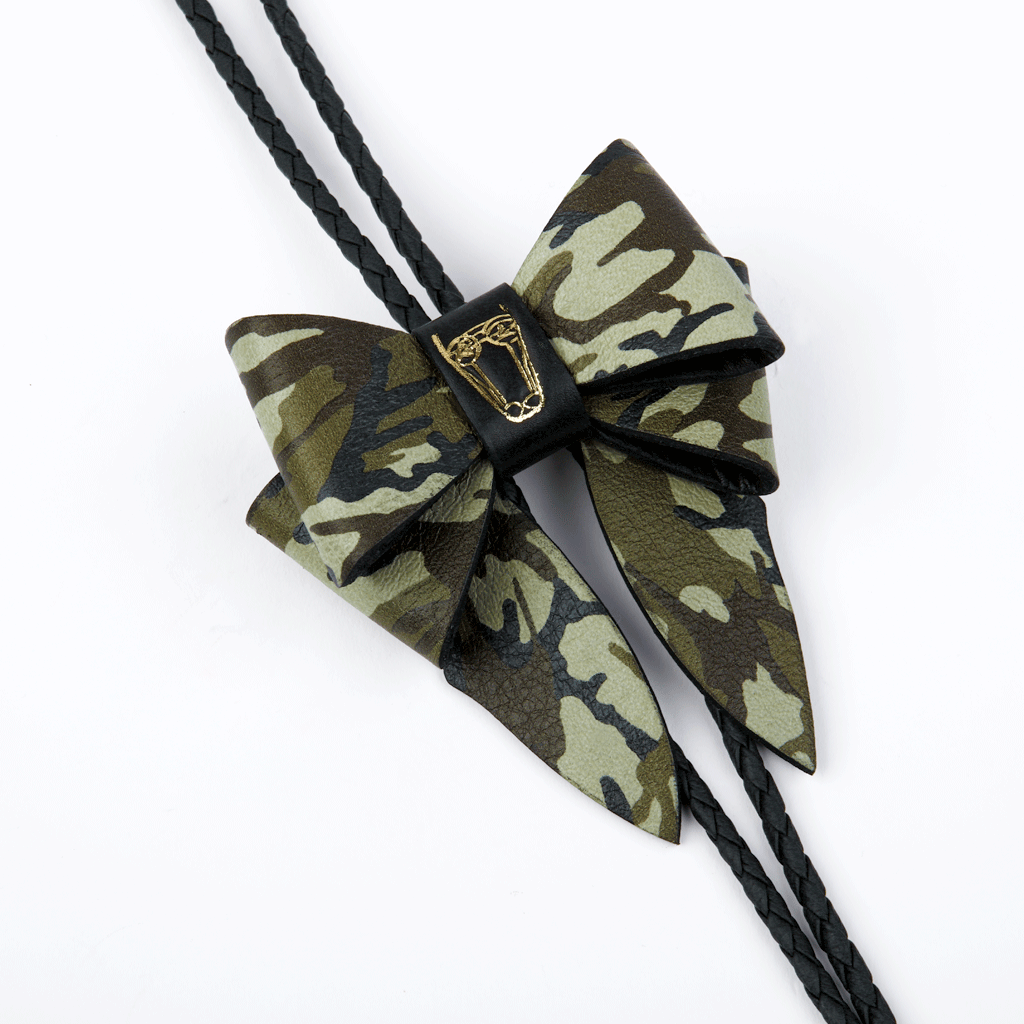 This statement piece combines our Marrs Makers signature leather bow with the swagger of a bolo tie; the functionality of a necklace and the drama of a choker.   Smooth finish, camouflage printed Saffiano leather bow with Marrs Makers embossed horse mascot. Bolo slide clip on reverse adjusts braided leather cord length, then fastens in place. Gold plated, Marrs Makers bolo tips.