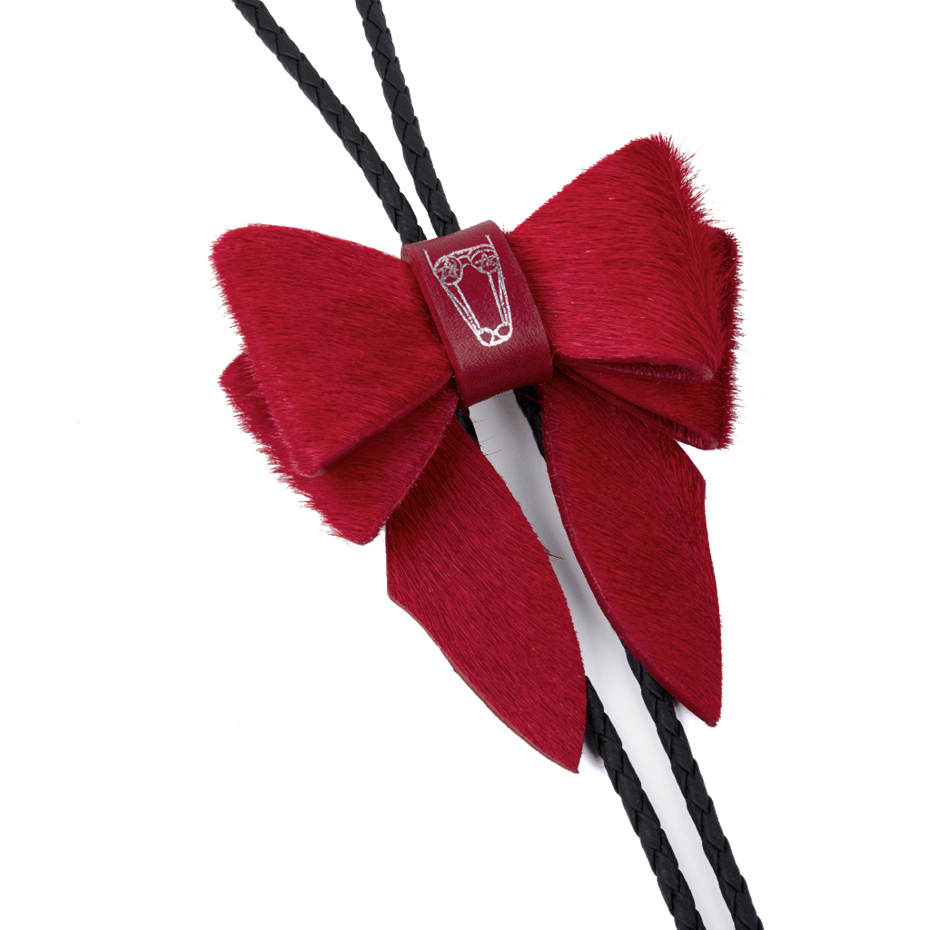 This statement piece combines our Marrs Makers signature leather bow with the swagger of a bolo tie; the functionality of a necklace and the drama of a choker. Scarlet Calf Hair Leather bow with Marrs Makers embossed horse mascot. Bolo slide clip on reverse adjusts braided leather cord length, then fastens in place. Nickel plated bolo tips.