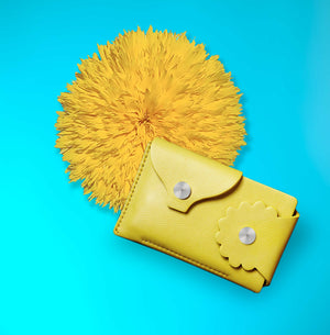 Marrs Makers Marigold Yellow Leather Wallet. Bright turquoise background color with large sunflower in this product shot.