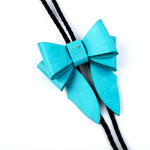 This statement piece combines our Marrs Makers signature leather bow with the swagger of a bolo tie; the functionality of a necklace and the drama of a choker.   Smooth finish, turquoise calf leather bow with Marrs Makers embossed horse mascot. Bolo slide clip on reverse adjusts braided leather cord length, then fastens in place. Nickel plated bolo tips.