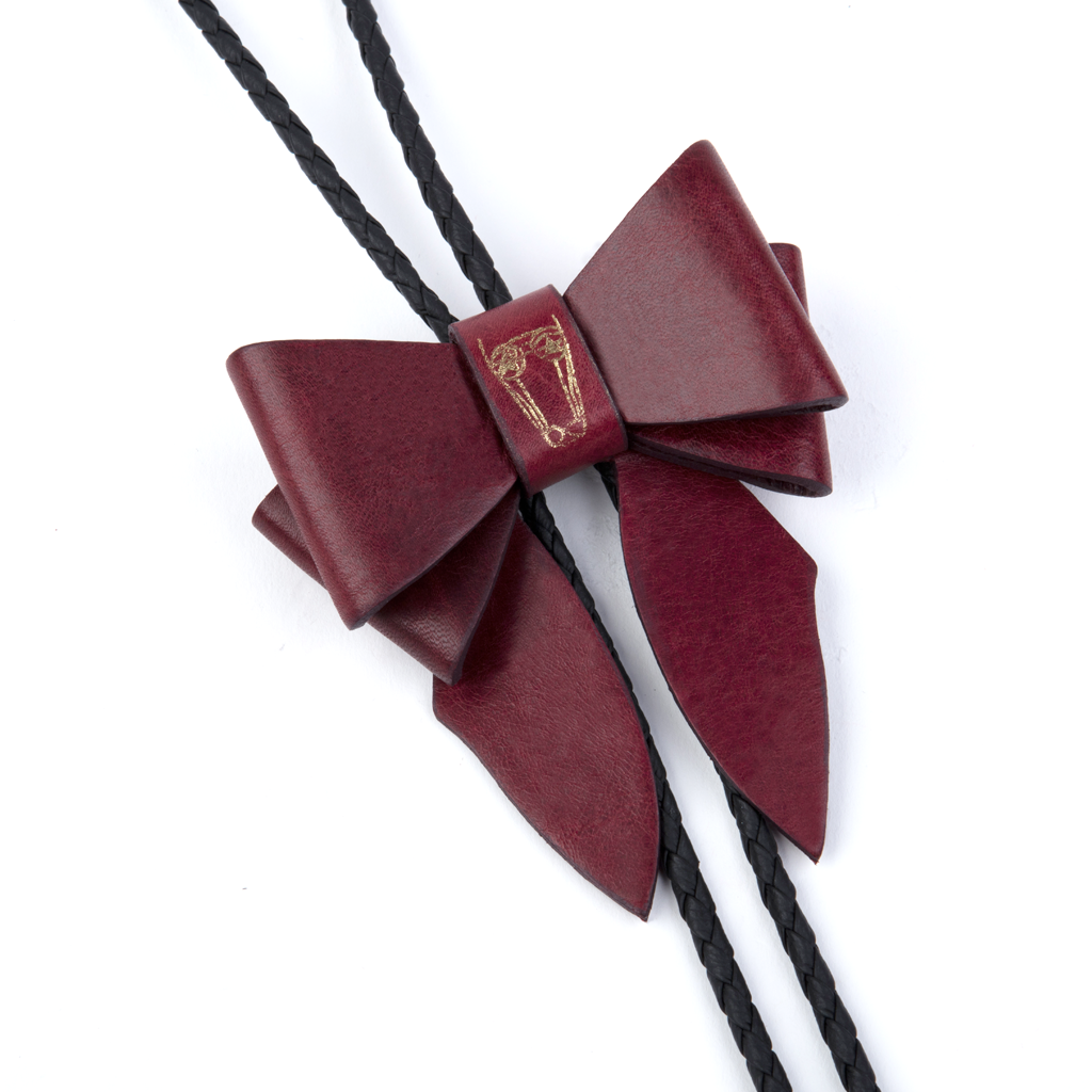 This statement piece combines our Marrs Makers signature leather bow with the swagger of a bolo tie; the functionality of a necklace and the drama of a choker.   Smooth finish, solid calf leather bow with Marrs Makers embossed horse mascot. Bolo slide clip on reverse adjusts braided leather cord length, then fastens in place. Gold plated, Marrs Makers bolo tips.