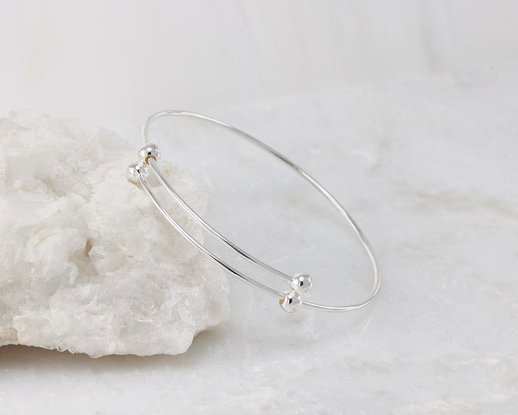 Silver adjustable bangle bracelet on white rock