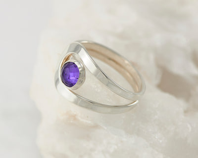 Silver amethyst wrap ring on white rock