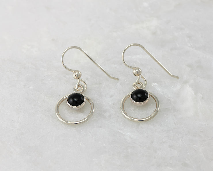 Silver polished black onyx earrings on white marble