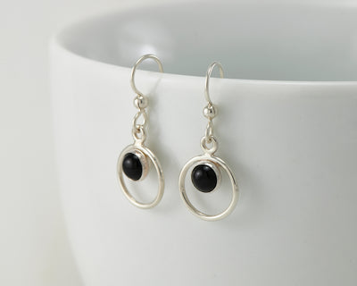 Silver black onyx earrings on white cup
