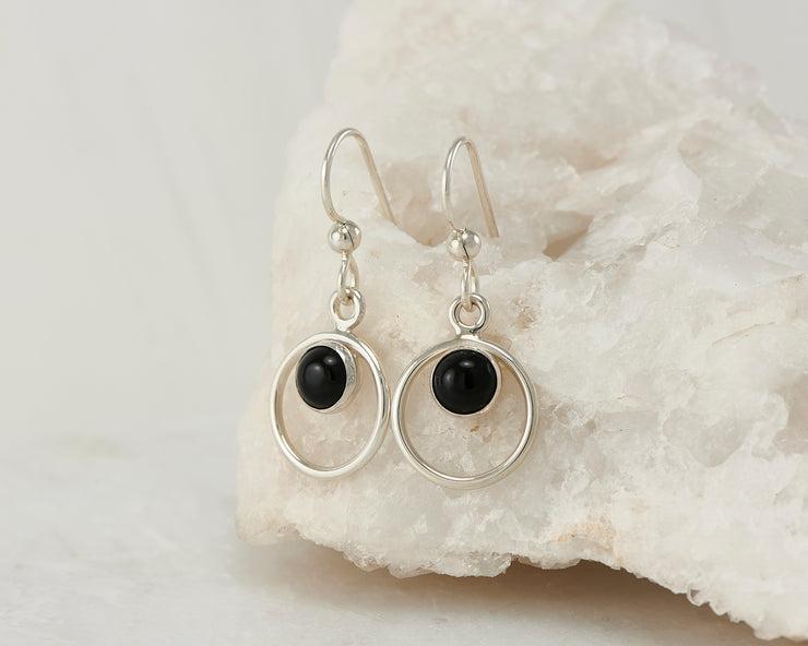 Silver black onyx hoop earrings on white rock