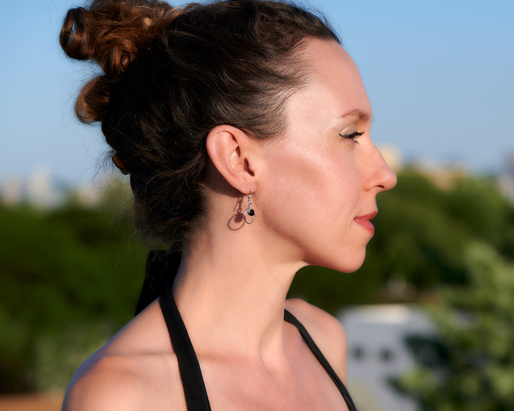 Woman wearing silver hoop black onyx earrings