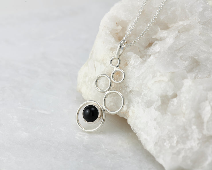 Silver black onyx pendant leaning on white rock