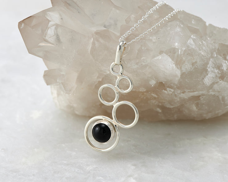 Silver black onyx pendant on crystal rock