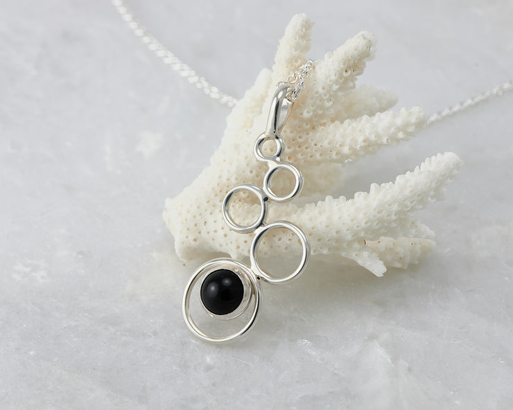 black onyx gemstone silver necklace on coral
