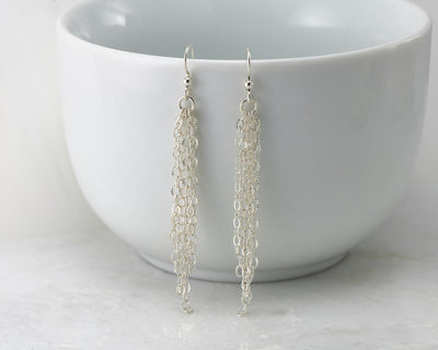 Silver chandelier earrings on white cup