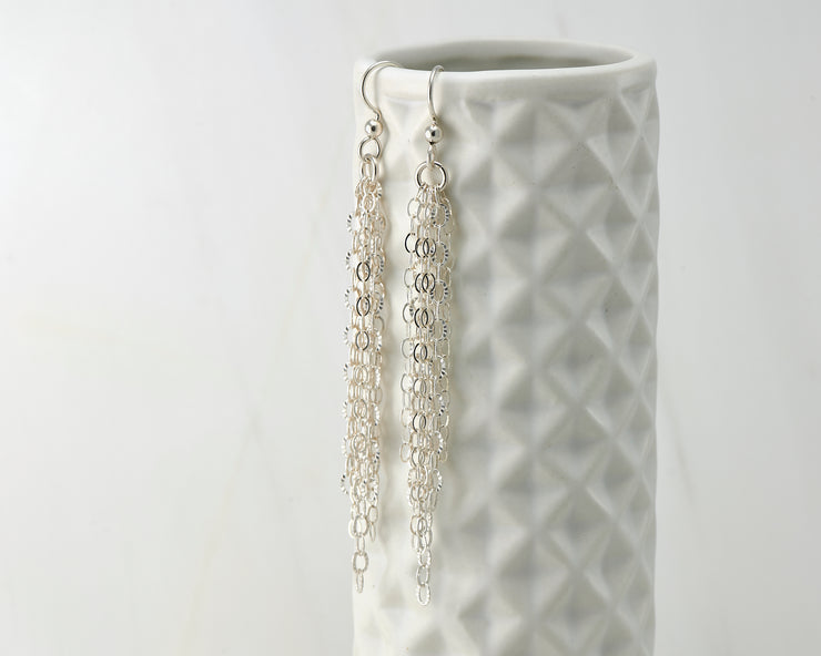 Silver chandelier earrings on geometric vase