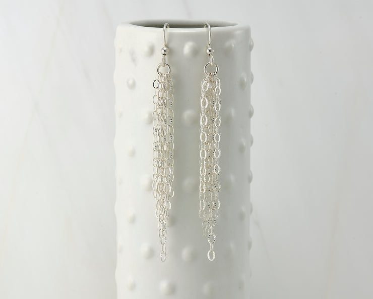 Silver chandelier earrings on dotted vase
