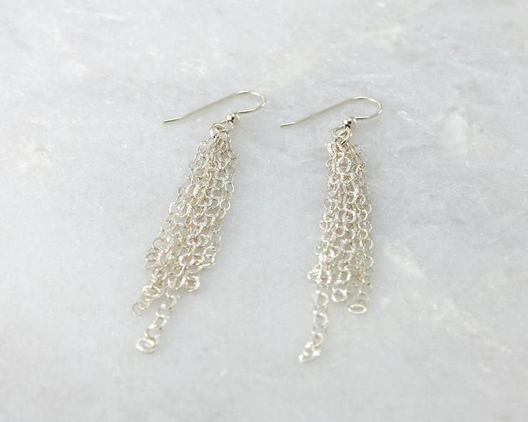 Silver chandelier earrings on white marble