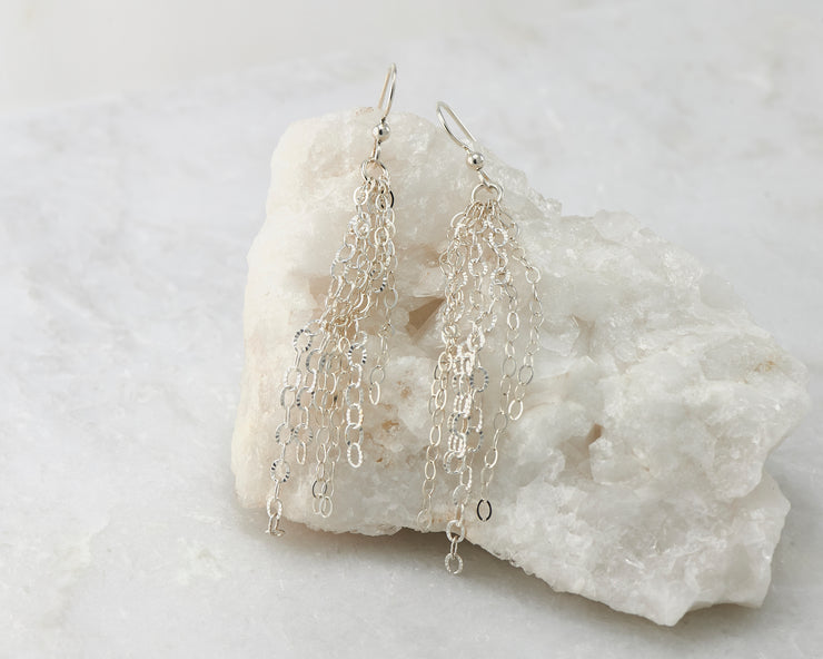 Silver chandelier earrings on white rock