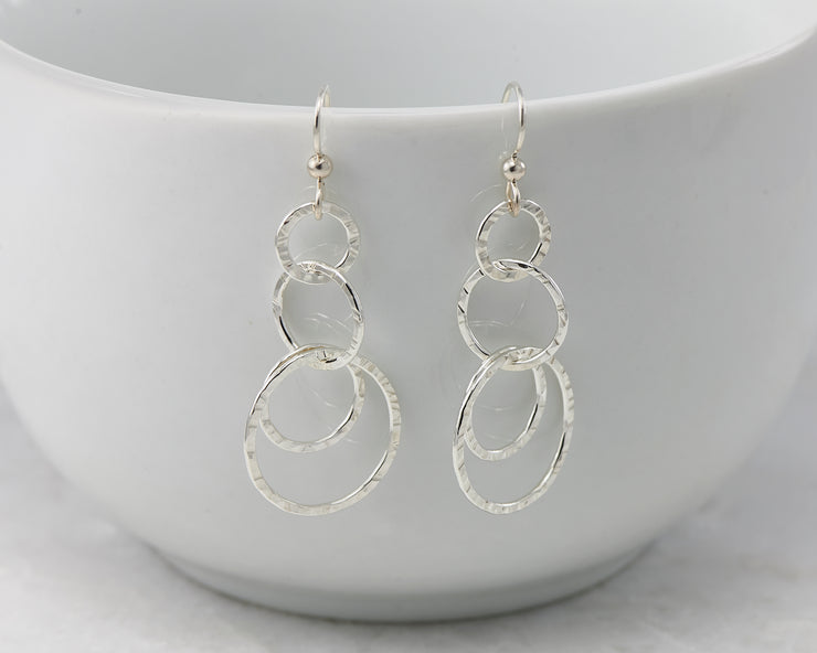 Silver hammered circles earrings on white cup