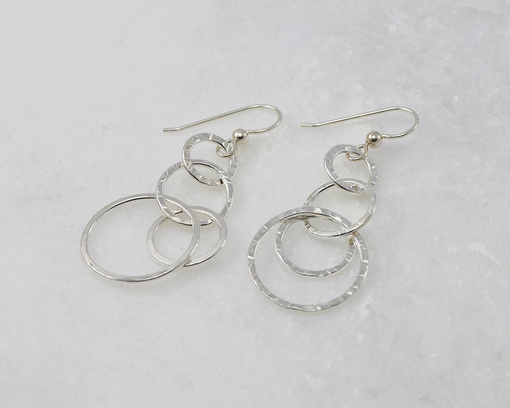 Silver polished hammered circles earrings on white marble