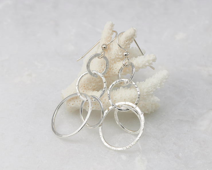 Silver hammered circles earrings on coral