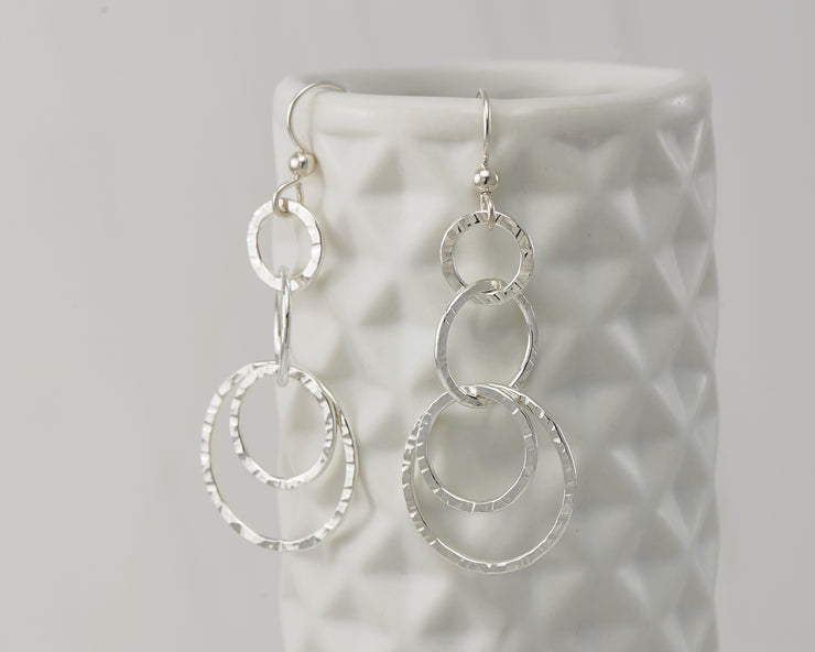 Silver hammered circles earrings on geometric vase