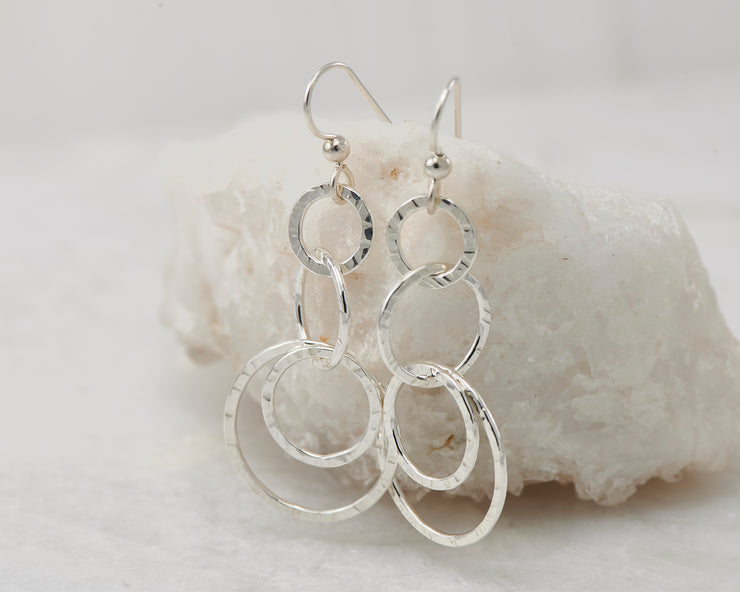 Silver hammered circles earrings on white rock