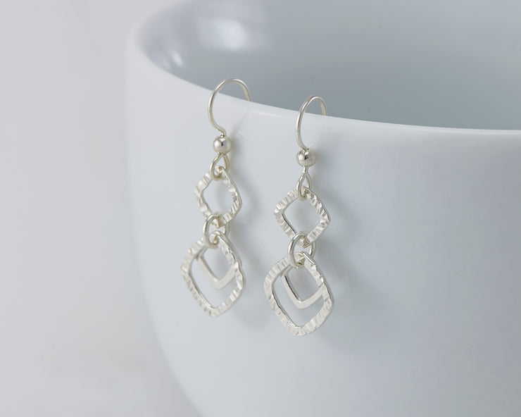 Silver hammered squares earrings on white cup