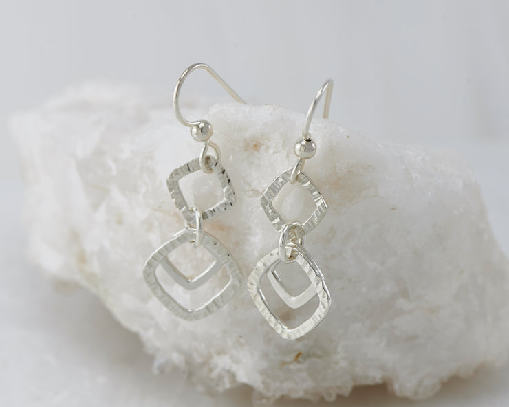 Silver hammered squares earrings on white rock