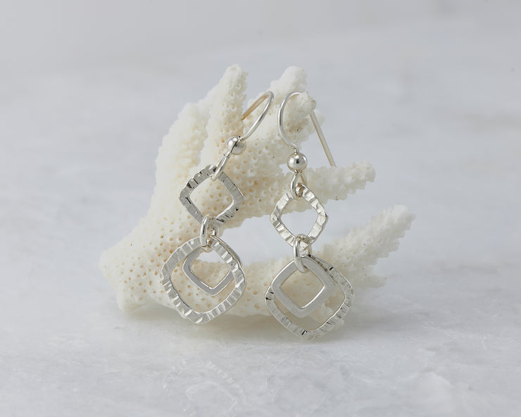 Silver hammered squares earrings on coral