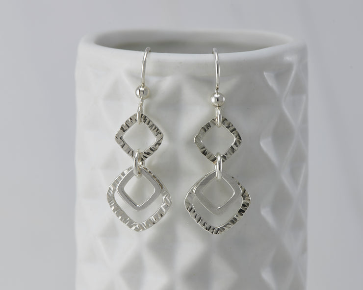 Silver hammered squares earrings on geometric vase
